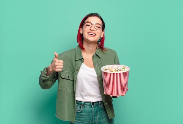 Bella donna dai capelli rossi con popcorn e telecomando per la tv