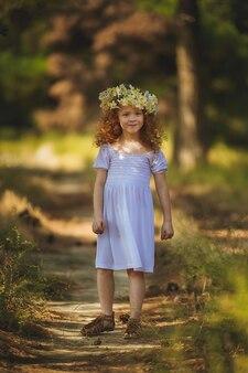 Ragazza dai capelli rossi che cammina nel bosco con i fiori