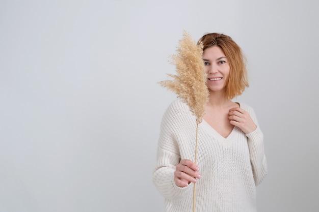 La donna dai capelli rossi tiene l'erba della pampa nelle mani. stelo di canna, erba di pampa essiccata, composizione di piume decorative per la casa, tema spiaggia, nuovo arredamento alla moda per la casa.