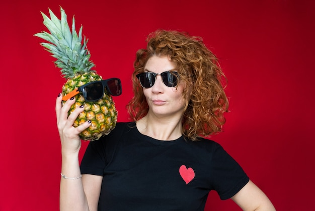Bella dai capelli rossi in una maglietta nera con una stampa di cuore tiene un ananas tra le mani su uno spazio rosso