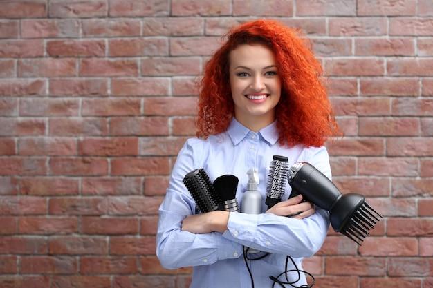 Bella ragazza dai capelli rossi con accessori da barbiere