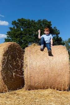 Un ragazzo dai capelli rossi siede in cima a una pila di paglia dorata in un campo