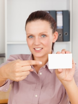 Donna d'affari dai capelli rossi che punta a una carta
