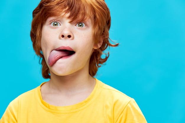 Il bambino dai capelli rossi tira fuori la lingua di lato apre gli occhi spalancati maglietta gialla sfondo blu
