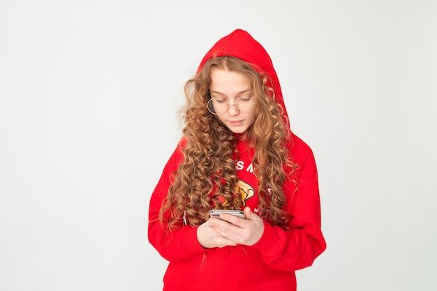 Ragazza adolescente capelli ricci dai capelli rossi in felpa con cappuccio rossa con cappuccio, utilizzando e leggendo smartphone su priorità bassa bianca.