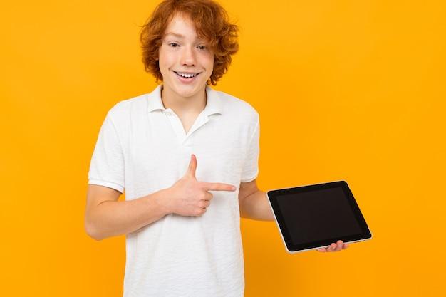 Il consulente adolescente riccio dai capelli rossi in un negozio in una maglietta bianca mostra un display tablet con un mockup su uno sfondo giallo