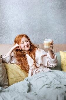 Ragazza carina dai capelli rossi con una tazza di caffè si gode la vita la mattina presto nel suo letto. Foto Premium