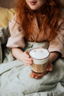 Ragazza dai capelli rossi a letto con una tazza di caffè con schiuma di latte.