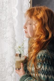 La ragazza dai capelli rossi beve il suo caffè mattutino da un bicchiere di vetro.