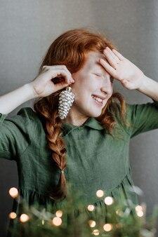 Una ragazza dai capelli rossi con un vestito di lino verde si è fatta una decorazione per le sue orecchie da un giocattolo dell'albero di natale.