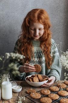 La ragazza dai capelli rossi fa colazione con biscotti al latte e farina d'avena.