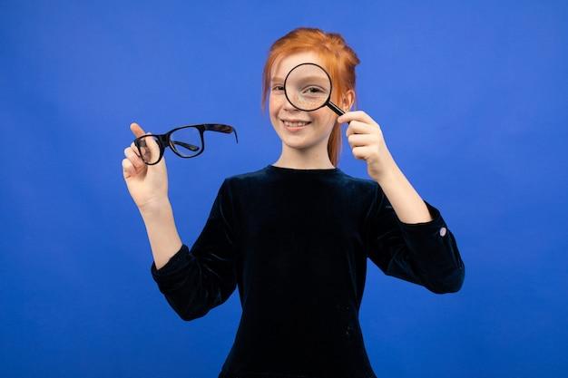 Ragazza dai capelli rossi che tiene i vetri per vista e una lente d'ingrandimento su un blu