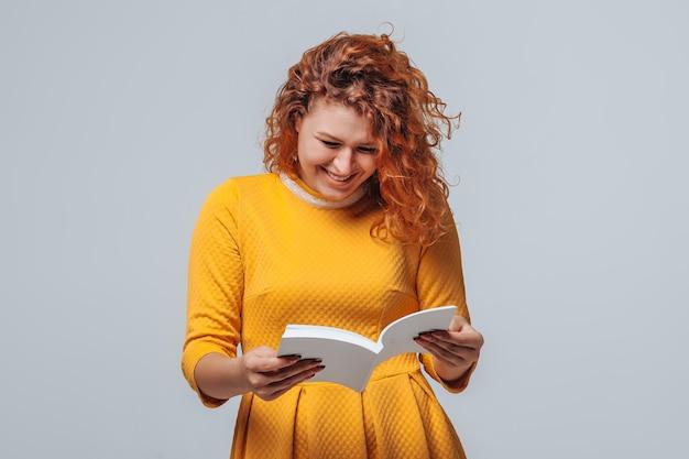 Ragazza dai capelli rossi che legge un libro bianco su sfondo grigio chiaro.