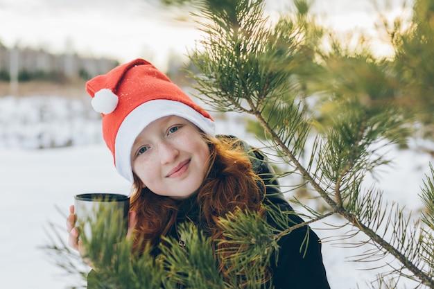 Una ragazza dai capelli rossi con un cappello da babbo natale sta bevendo il tè tra i rami di abete.