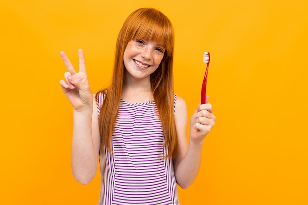 La ragazza dai capelli rossi sorride e tiene uno spazzolino da denti in mano su uno sfondo giallo