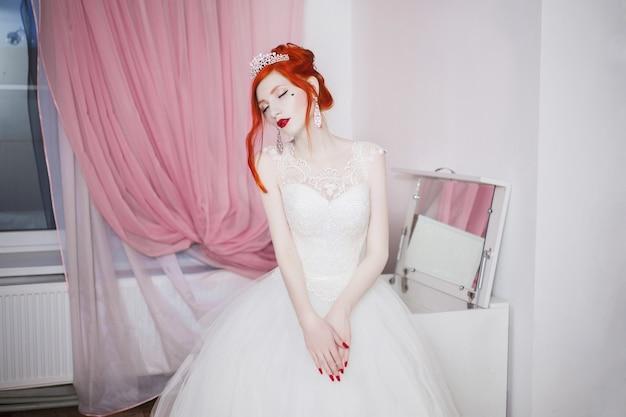 Ragazza dai capelli rossi in un abito da sposa, aspetto insolito brillante, unghie rosse, una ragazza con la pelle pallida, bellissimo abito da sposa, un cuore sulla guancia, trucco luminoso, su una modella fetish bianca