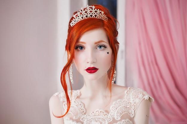 Ragazza dai capelli rossi in un abito da sposa
