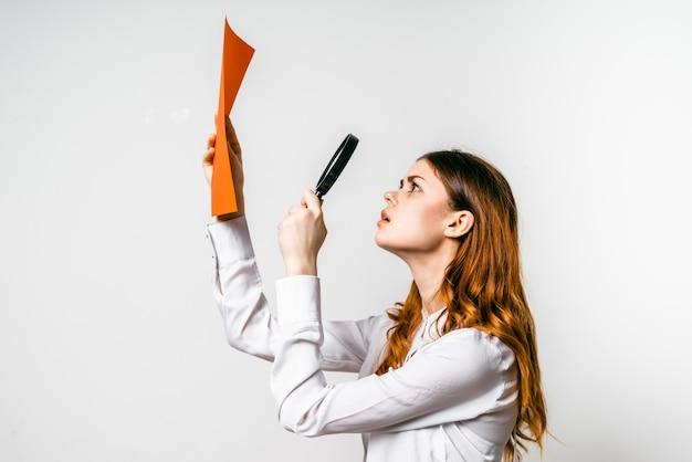 Una ragazza dai capelli rossi con una camicia bianca guarda un foglio a4 arancione attraverso una lente d'ingrandimento