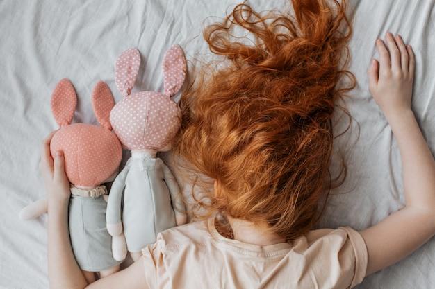 Ragazza dai capelli rossi con bambole sul letto.