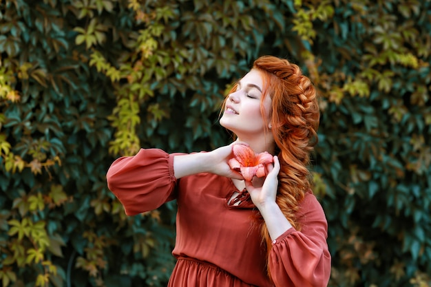Ragazza dai capelli rossi con un fiore in giardino