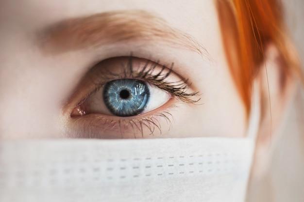 Ragazza dai capelli rossi con una mascherina medica su un bianco, donna medico, femmina occhio blu, macro, garza