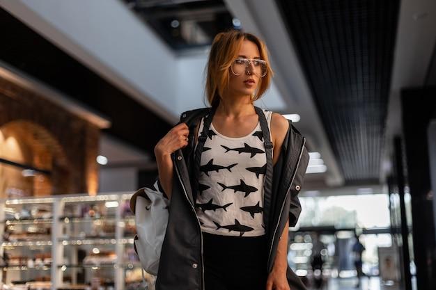 Splendida giovane donna dai capelli rossi in una giacca vintage in una maglietta con gli occhiali in una maglietta con un motivo di bancarelle in un negozio moderno. modello di ragazza abbastanza attraente alla moda cammina sul negozio.