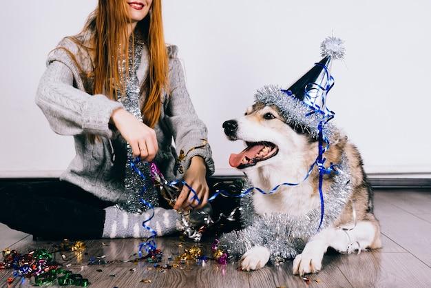 Ragazza felice dai capelli rossi seduta sul pavimento con il suo grosso cane che celebra il nuovo anno e il natale
