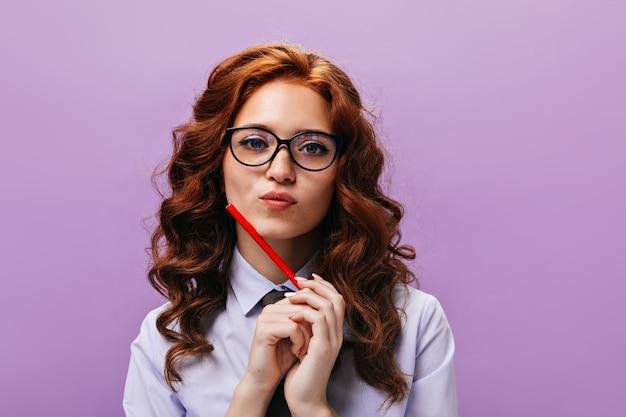 La signora dai capelli rossi in camicia blu e occhiali da vista posa pensierosa con una matita rossa