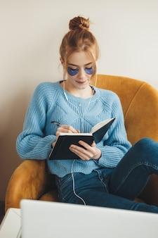Signora dai capelli rossi con le lentiggini che indossa i percorsi degli occhi di idrogel mentre ascolta la musica e legge un libro sulla poltrona