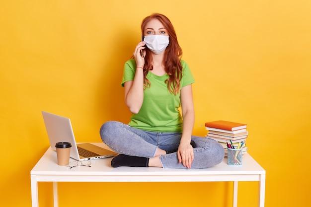 Bella ragazza dai capelli rossi parla al telefono mentre era seduto sulla scrivania