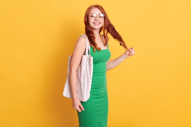 Ragazza sorridente dai capelli rossi con il sacchetto di cotone bianco bianco