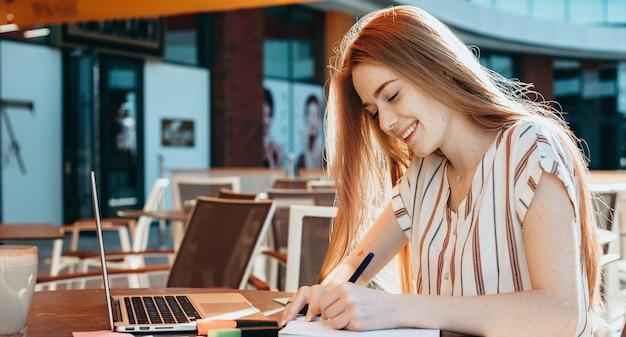 Studente dai capelli rossi con le lentiggini che fa i compiti al computer in una caffetteria scrivendo un libro e un sorriso