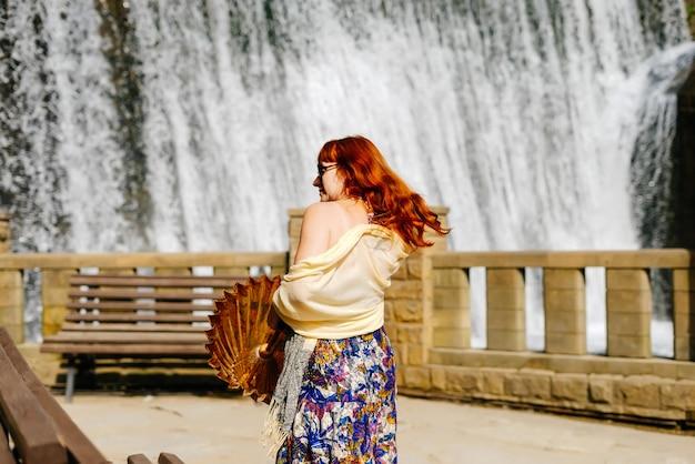 La ragazza alla moda dai capelli rossi cammina attraverso il parco al sole sullo sfondo di una cascata