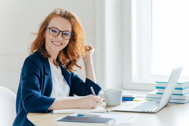 La donna dai capelli rossi analizza i dati e redige un rapporto contabile