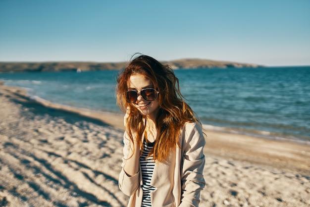 Donna dai capelli rossi sulla spiaggia con gli occhiali vicino al modello di t-shirt cappotto beige mare