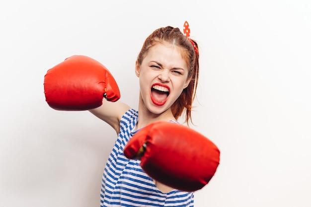 Donna dai capelli rossi in guanti è impegnata nella boxe su un'aggressione di modello sfondo chiaro