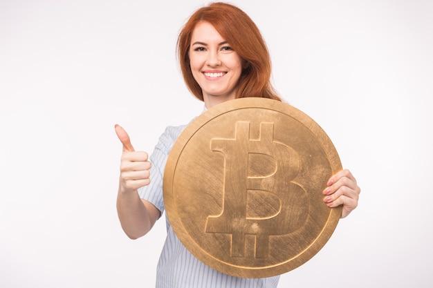 Donna dai capelli rossi che tiene grande bitcoin e che mostra i pollici in su su priorità bassa bianca. criptovaluta