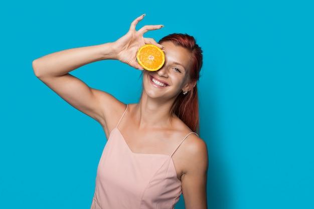 La donna dai capelli rossi si copre gli occhi con un limone a fette in posa su una parete blu dello studio