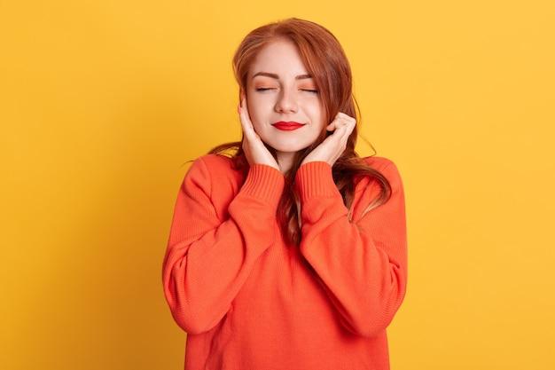 Donna dai capelli rossi tappando le orecchie con le dita e chiudendo gli occhi, non volendo ascoltare musica ad alto volume