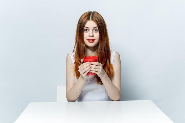 Donna dai capelli rossi che si siede al tavolo con una tazza di bevande emozioni di rilassamento