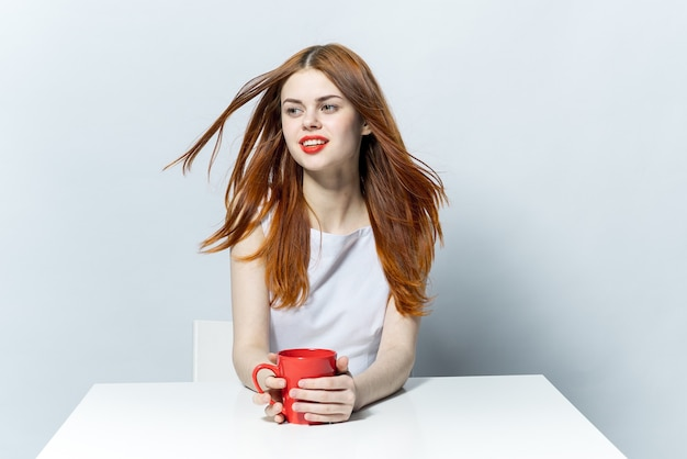 Donna dai capelli rossi seduta al tavolo con una tazza di bevanda relax