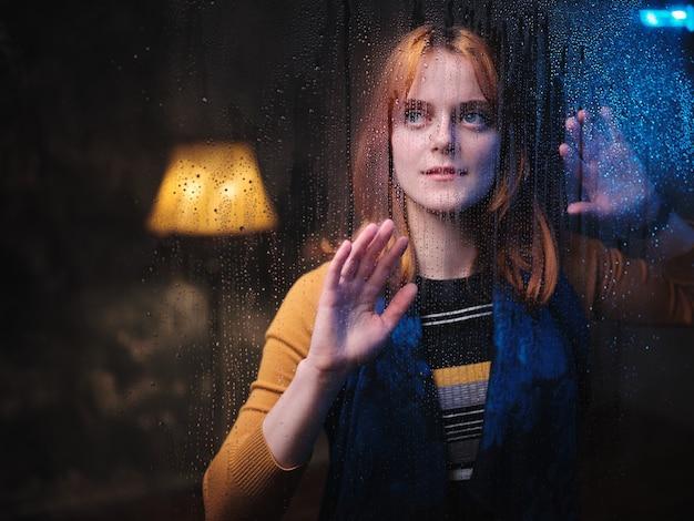 Una donna dai capelli rossi sta alla finestra con le gocce di pioggia