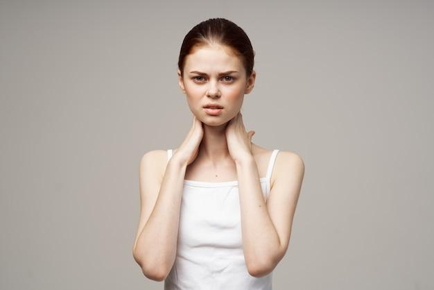 Donna dai capelli rossi che si tocca con la maglietta bianca delle mani