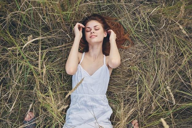 La donna dai capelli rossi in un abito bianco si trova su un pagliaio all'aperto modello di aria fresca