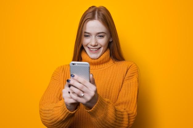 Donna dai capelli rossi con le lentiggini in chat sul cellulare e indossa un maglione su una parete gialla