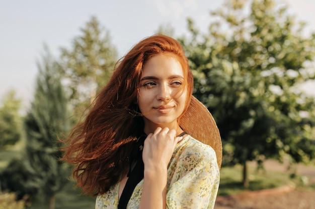 Giovane donna dai capelli rossi con graziose lentiggini e occhi marroni in abiti verdi alla moda e cappello di paglia che sorride e distoglie lo sguardo all'aperto