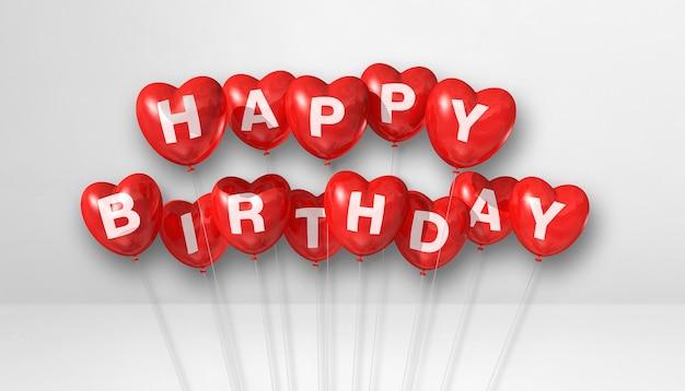 Palloncini d'aria a forma di cuore rosso buon compleanno su una scena di superficie bianca