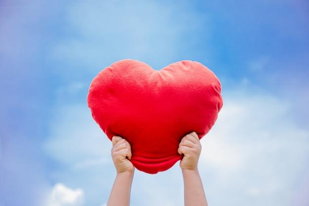 Red hart in mano con sky bule