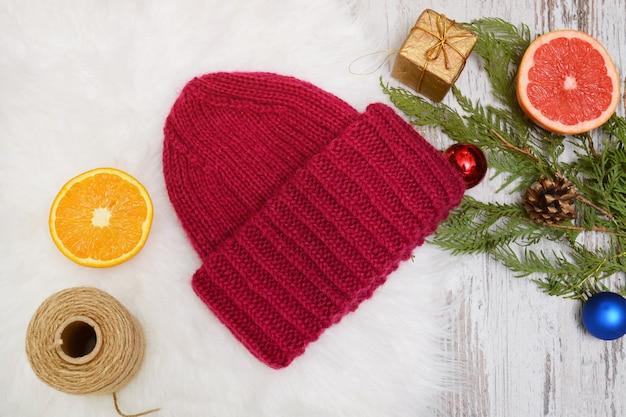 Cappello rosso, agrumi e addobbi per l'albero di natale