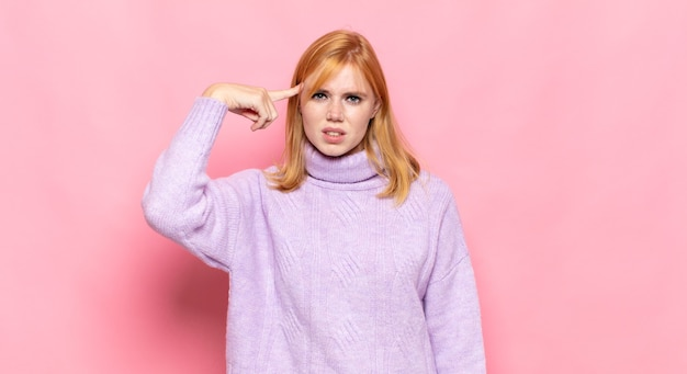 Bella donna dai capelli rossi che si sente confusa e perplessa, dimostrando che sei pazzo, pazzo o fuori di testa